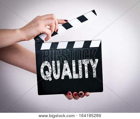 Quality. Female hands holding movie clapper. Gray background