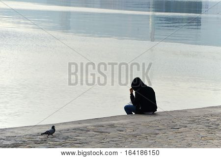 Man reading a book on the city's waterfront