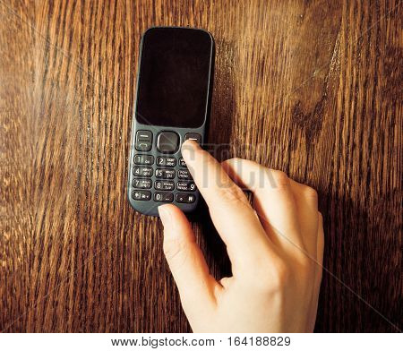 Womans hand using classic cell phone blank screen top view