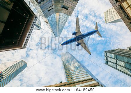 Airplane above Hong Kong city Central District High-rise buildings in the blue sky. Concept of transport, travel and business. View from the ground level.