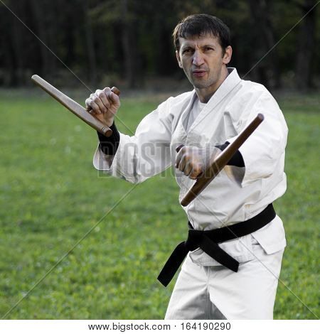 Master of martial arts in white kimono is practicing with tonfa.