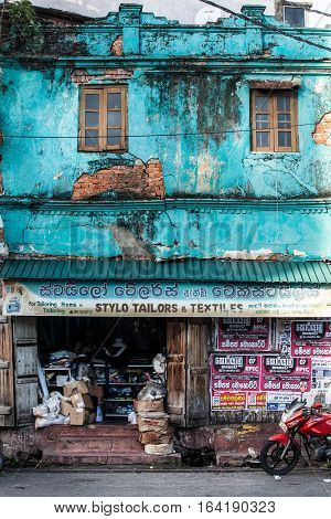 GALLE, SRI LANKA. August 1, 2016: Old and worn colorful building at Galle in Sri Lanka. An old building in light blue. business on the ground floor. Urban scene in Galle, southern town in Sri Lanka.