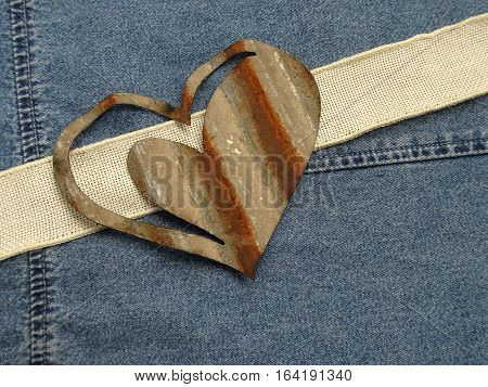 A rusty heart crafted from corrugated metal, an ivory burlap ribbon, and a denim background create a rustic approach to love and friendship.  Copy space.