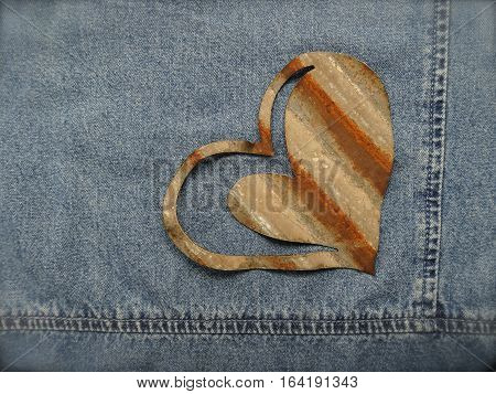 A rusty heart crafted from corrugated metal and the corner seams of a jean jacket create a rustic background for sentiments of love and friendship.  Copy space.