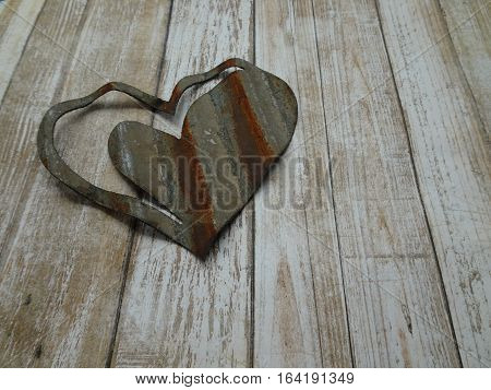 A rusty heart crafted from corrugated metal with a background of white peeling paint creates a rustic image for sentiments of love and friendship.  Copy space.