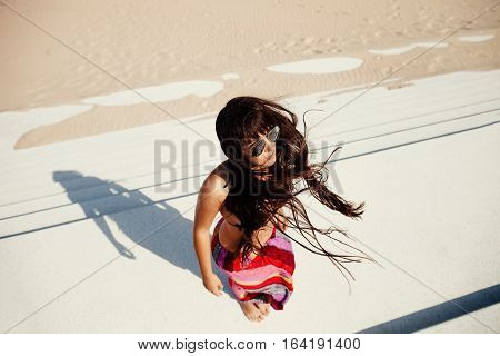 wind in hair of sexy woman on beach. Motion. Top view