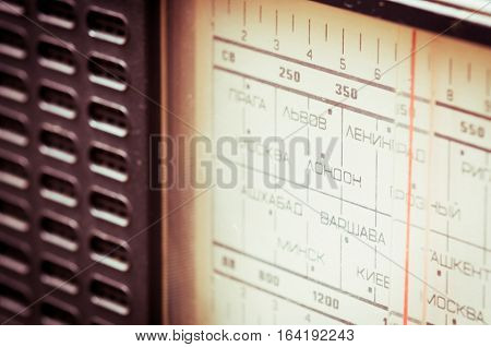 Close up photo of soviet radio. On the panel are listed the names of cities and capitals of the Soviet Union and Europe in Russian, such as Moscow, Kiev, Lviv, Minsk, Warsaw