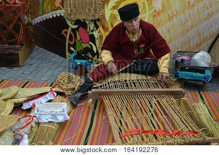 March 19, 2015, Baku Azerbaijan. Fair dedicated to the celebration of Novruz holiday. The old man is busy weaving in national dress