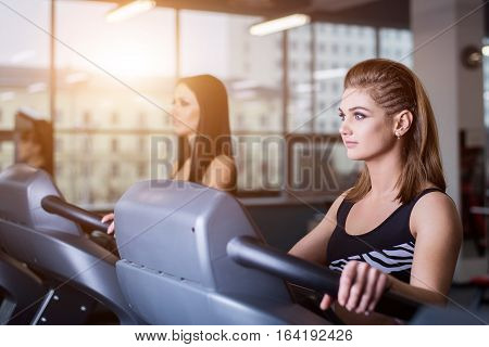Sexy fit women running on treadmills in modern gym. Healthy young girls doing running exercise on treadmill in gym