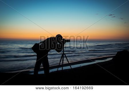 Silhouette of a photographer at morning sunrise