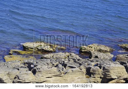 Fishing rod on a rocky sea shore