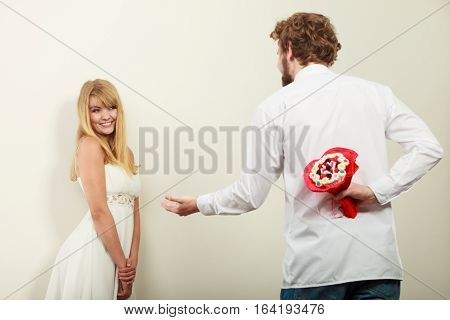 Man holding candy bunch flowers. Boyfriend with surprise present gift for pretty woman girlfriend. Happy loving couple. Love.