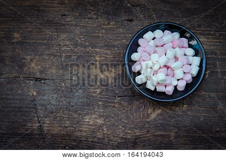 Pink and white mini marshmallows in a black plate on a wooden background with place for text. Different mini puffy marshmallows. Marshmallow concept. Top view. Copy space.