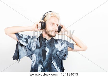 Young people relax and passion concept. Passionate music lover stylish guy with headphones listening music relaxing enjyoing studio shot on white