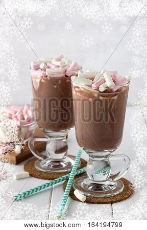 Tasty cocoa drink with coloful marshmallows in two glasses on white wooden table. Chocolate beverage with paper straws.