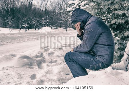 Man sitting on bench in a forest in winter with snow on the ground