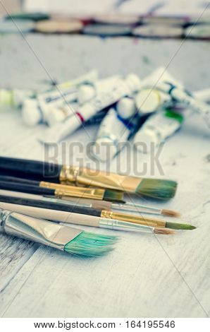 Artist paint brushes and oil paint tubes on white wooden background. Brush paint artistic. Tools for creative work. Back to school. Paintings Art Concept. Selective focus. Copy space.