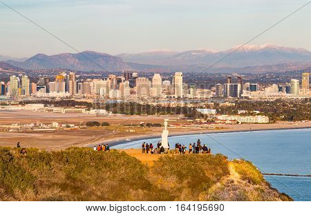 SAN DIEGO, CALIFORNIA - DECEMBER 26, 2016:  Sightseeing tourists enjoy the view from Cabrillo National Monument with the city skyline and snow-capped mountains in the background.
