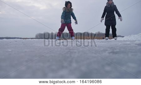 People skate on skating rink in the winter on ice, active winter holiday family sports
