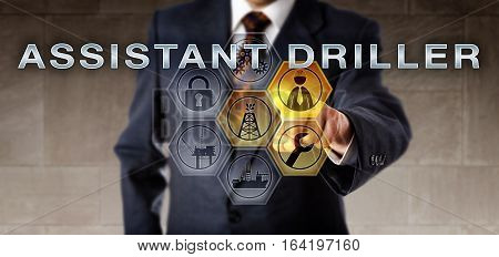 Recruitment agent in blue suit activating ASSISTANT DRILLER on a virtual remote control screen. Oil and gas industry job metaphor for the professional role of an operator of drilling equipment.