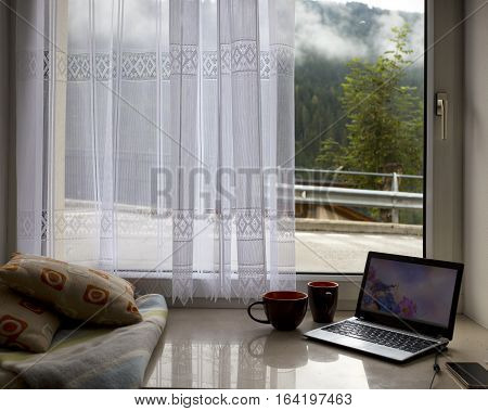 wonderful morning in the mountains. pillows plaid laptop cup of coffee on the windowsill and the landscape outside the window