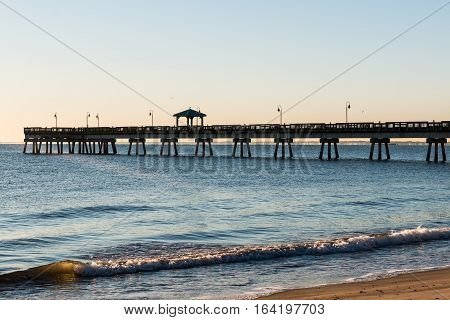 Fishing pier with waves at Buckroe Beach in Hampton, Virginia at sunrise.