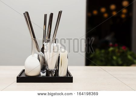 Flatware with napkin and toothpicks in evening cafe.