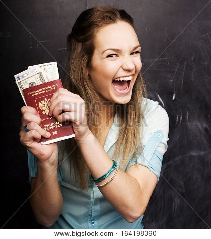 portrait of cute girl student with money and passport in classroom