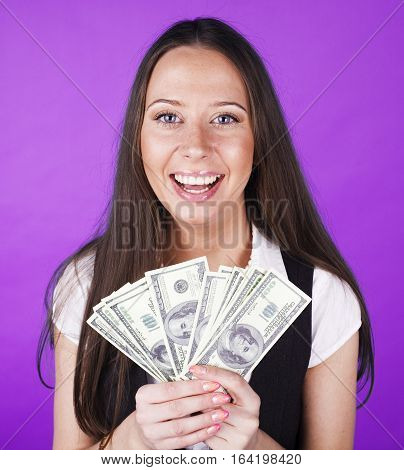 pretty young brunette real modern woman with money cash on blue background happy smiling, lifestyle people concept close up