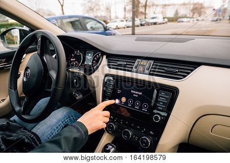 PARIS FRANCE - DEC 13 2016: Woman pressing Home screen on the Apple CarPlay main screen in modern car dashboard. CarPlay is an Apple standard that enables a car radio or head unit to be a display and controller for an iPhone. It is available on all iPhone