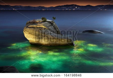 Bonsai Rock, Lake Tahoe, Nevada with underwater light painting.  Glowing water surrounds this iconic landscape feature.