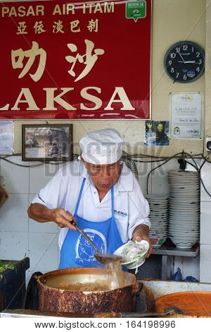PENANG MALAYSIA-29 DECEMBER 2016: Hawker vendor at their Assam Laksa noodle stall in Air Itam Penang Malaysia. Assam Laksa is ranked 7th most delicious food in the world by CNN.