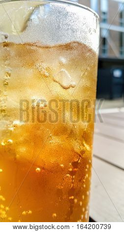 Closeup of a glass of ice cold drink. Subject against a blurred (bokeh) out urban environment with some backlighting.