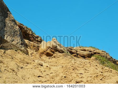Rocky slope with the trodden sand road