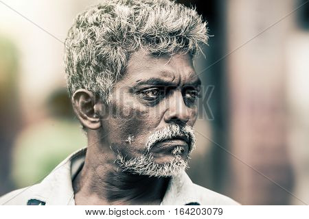 KANDY, SRI LANKA. July 24, 2016: Portrait of a man in Kandy in Sri Lanka. The man has a beard and graying hair, intense eyes, suggestive expression.