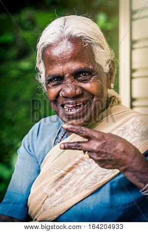 NUWARA ELIYA, SRI LANKA - July 25, 2016: Happy old indian woman in Nuwara Eliya in Sri Lanka. A smiling elderly black woman with a wrinkled face. White hair and worn teeth. The woman is wearing the typical Indian dress: Sari.