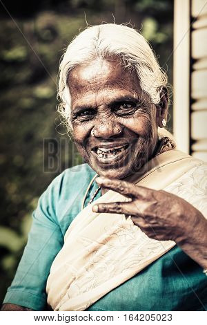 Happy old indian woman. Elderly wrinkles. A smiling elderly black woman with a wrinkled face. White hair and worn teeth. The woman is wearing the typical Indian dress: Sari. Location: Nuwara Eliya, Sri Lanka. 2016