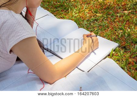 Pretty girl or women write something in notebook with a pencil. And she lay down to white cloth or fabric on ground of green grass or lawn in the public park.