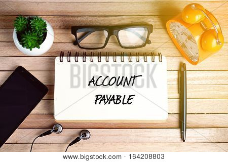 Top view of earphone, smartphone, plant, eye glasses, alarm clock, pen and open notebook written with ACCOUNT PAYABLE on wooden background. Business Concept.