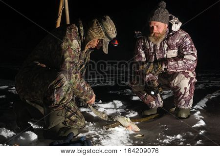 Two men are fishing by rod and changing lure at dark winter night
