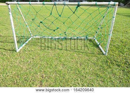 Empty net soccer goal football green grass field sunny day outdoors