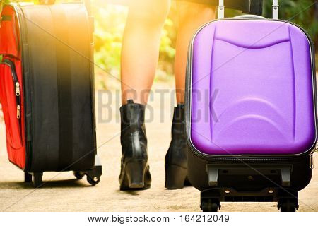 Person walk drag purple travel bag beside black car and red travel bag for travel and sun light