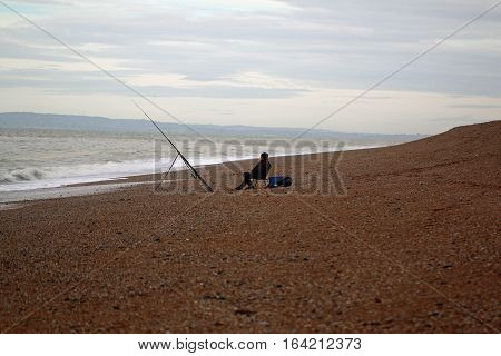 Lone fisher man on a shingle beach in the winter