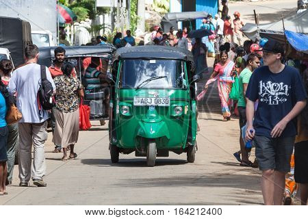 ELLA, SRI LANKA. July 27, 2016: Tuk-tuk auto rickshaw and tourists and local citizens strolling in the street in Ella in Sri Lanka. Bajay or Bajaj is a motorized development of the traditional pulled rickshaw or cycle rickshaw.