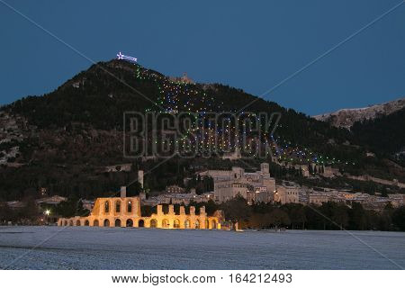 Panoramic view of medieval Gubbio village at night with snow
