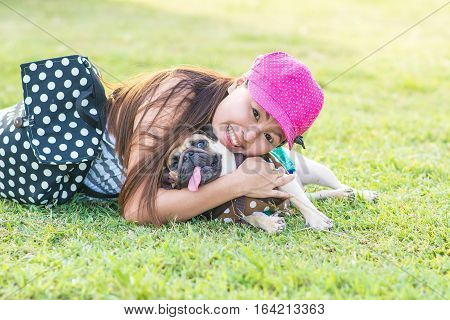 Portrait of a asian teenage woman girl hug with her cute dog puppy pug outdoors on fields