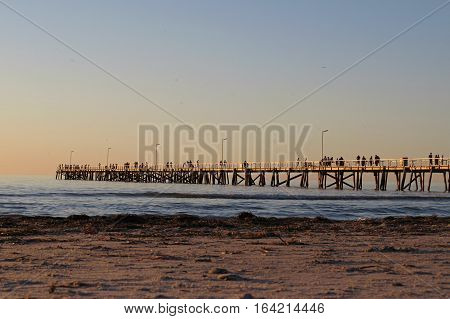 Australian beach sand with sunset golden sky silhouette of jetty and people