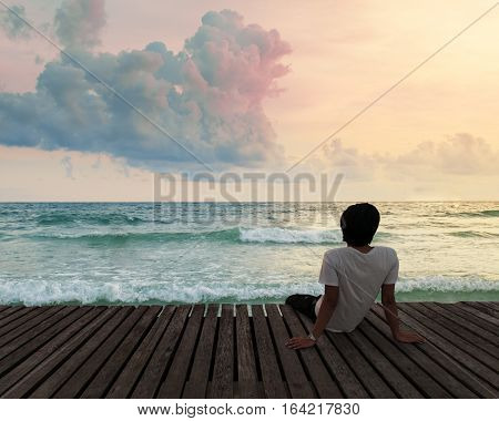 Lonely Man sitting in a wooden dock pier in sea beach with twilight sky in sunset time and think concentrate