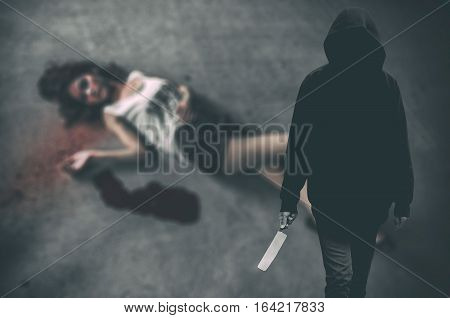 Murderer hooded man ready to attack to kill his victim that is the woman to died on ground. (Criminal concept) poster