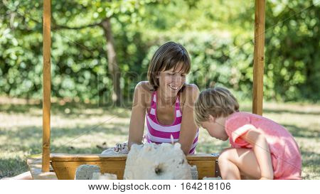 Happy young mother playing with her child in the garden smiling as she watches her being creative outdoors in a sand pit.